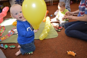 toddler with balloon at Signs and Sounds class