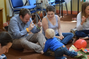 Mum, dad and toddler enjoying music and signing